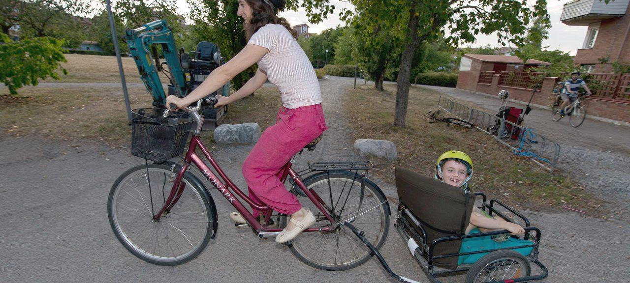 Kvinna cyklar med barn i cykelvagn.