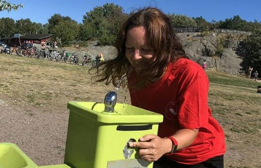 Kvinna dricker ur en fontän.