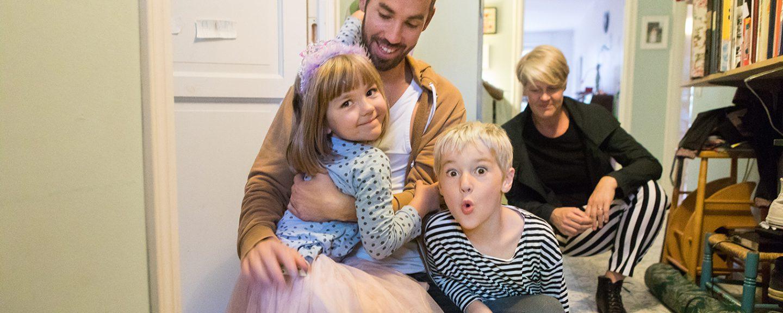 Två barn i pappas knä, mamman i bakgrunden i hallen i en hyresrätt. Foto: Erik Nordblad