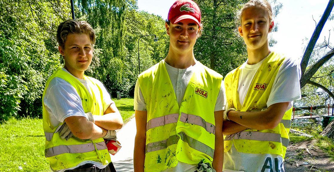 Tre glada unga killar på sommarjobb.