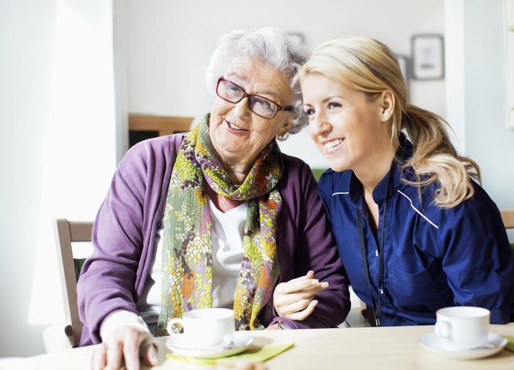 Glad pensionär på äldreboende tillsammans med personal