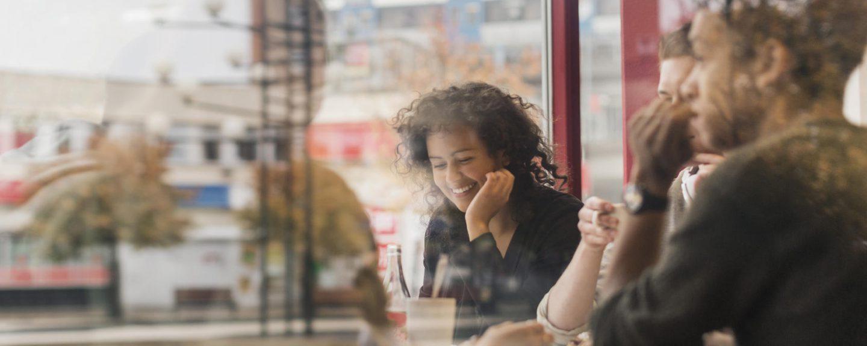 Ung glad kvinna sitter på kafé, genom fönster