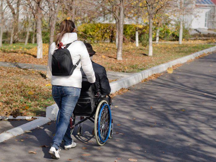 En kvinnlig personal puttar äldre i rullstol