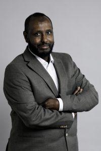 Rashid Mohammed, halvkropp i grå kavaj och vit skjorta mot vit bakgrund. Foto Jessica Segerberg