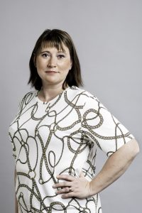 Sara Stenudd, halvkropp i vit mönstrad tröja mot vit bakgrund. Foto Jessica Segerberg
