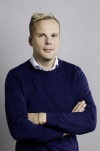 Tobias Johansson, halvkropp i blå tröja mot vit bakgrund. Foto Jessica Segerberg