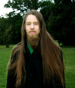 Halvkroppsbild på Rasmus som står i en grön park och ser in i kameran