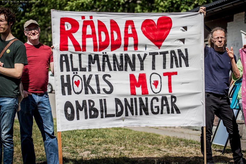 Bild på aktivister utomhus som håller upp en stor banderoll med texten: Rädda Allmännyttan. Hökis mot ombildningar