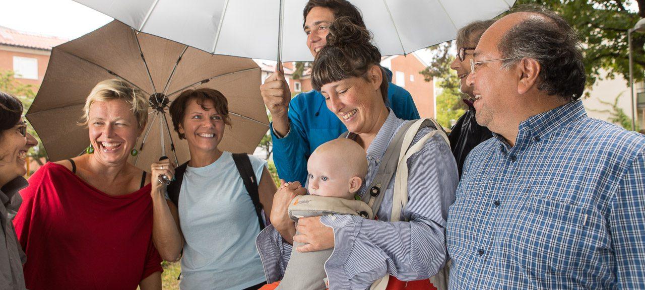 Glada människor står tillsammans under ett stort paraply. Foto: Erik Nordblad